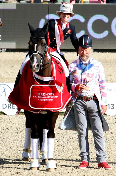 """Charlotte Dujardin brought some humor to the awards ceremony when she rode in on Valegro wearing a top hat that was part of the outfit of ringmaster Pedro Cebulka know for his flamboyant clothing at premier horse shows around the world. Pedro is wearing harlotte's """"crash"""" helmet that she took to wearing after being thrown from a horse and was knowcked out. Her helmet fits well with her top coat , she said, and expects that safety helmets will become the rule. ©2013 Ken Braddick/dressage-news.com"""
