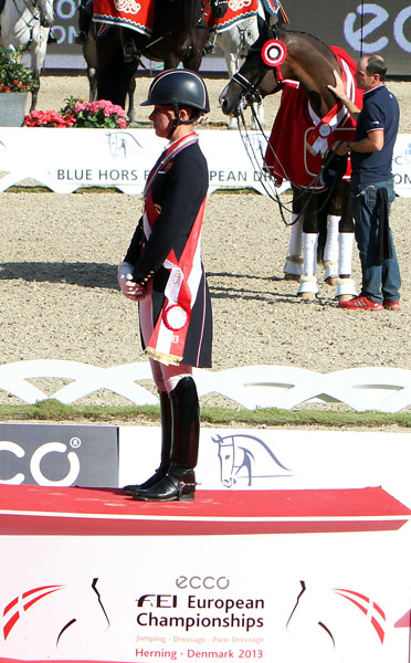 Valegro, used to medal ceremonies, turned to the British flag during the national anthem as did his rider, Charlotte Dujardin after winning the second individual gold medal at the European Xhampionships. ©2013 Ken Braddick/dressage-news.com