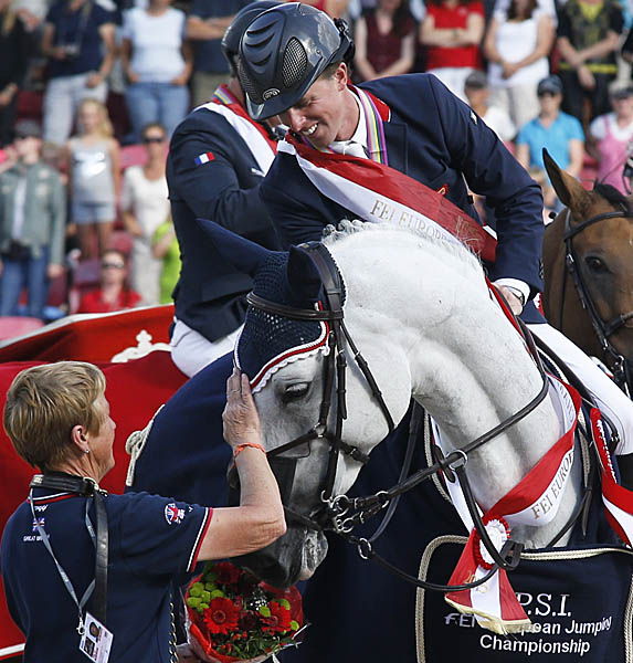 Cella being patted by groom Joy Montgomerie with Ben Maher looking on after the Jane Clark-owned horse won the individual silver medal at the European Championships. Ben and Cella led the Britain to the championship team gold two days earlier. © 2013 Jenny Abrahamsson/WorldofShowJumping.com
