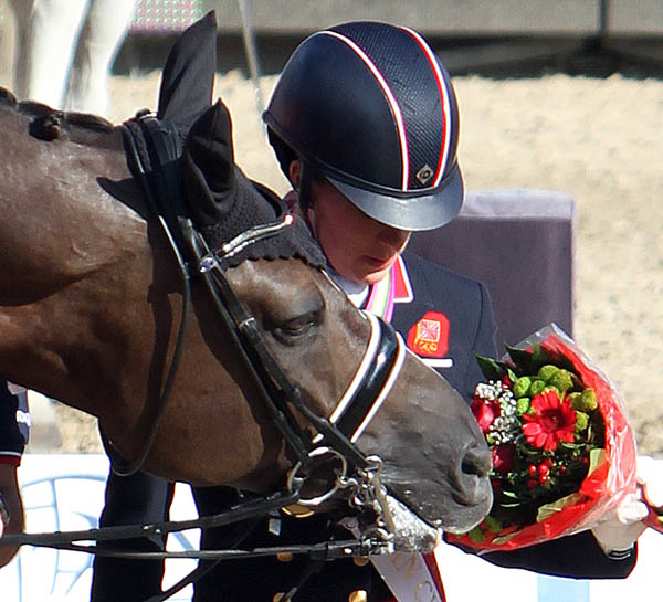 A moment when Valegro chewing on flowers held by Charlotte Dujardin is more important than the championships gold medal presentation,. © Ken Braddick/dressage-news.com