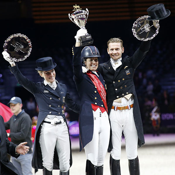 Charlotte Dujardin holding aloft the World Cup she won on Valegro for Great Britain's first title in the 29 years the championship has been held. © 2014 Jenny Abrahamsson/WorldofShowJumping.com