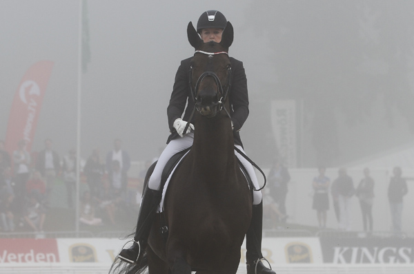 Denmark's Maria Anito Andersen peering between Svalegards Hottie's ears in the fog shrouded arena. © 2014 Ken Braddick/dressage-news.com