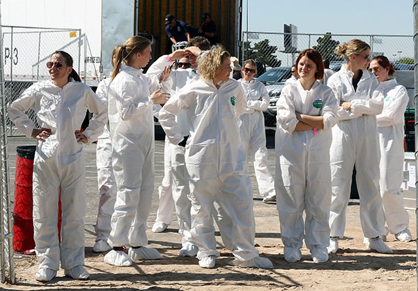 Grooms in hazmat suits at the stables that also is a quarantine center waiting for their horses to be unloaded at the Thomas & Mack Center for the World Cup Finals. © 2015 Ken Braddick/dressage-news.com