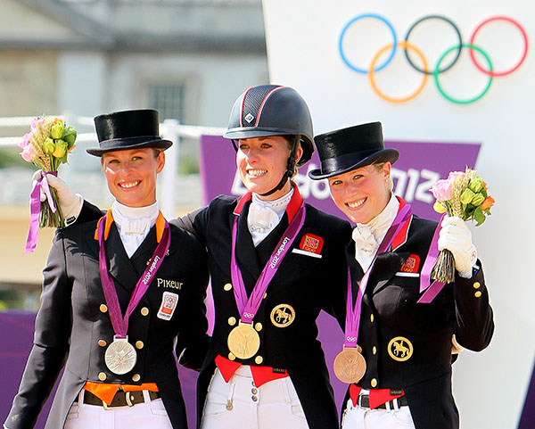 Adelinde Cornelissen (silver), Charlotte Dujardin (gold) and Laura Tomlinson (bronze) on the Olympic medals podium at the 2012 Olympic Games. ©Ken Braddick/dressage-news.com