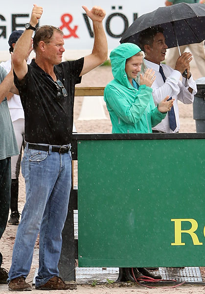 Michael Barisone in the rain cheering Allison Brock and Rosevelt at the end of their CDI4* Grand Prix ride, with U.S. coach Robert Dover under the umbrella. © 2016 Ken Braddick/dressage/news.com