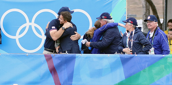 Ali Brock's ride led to lots of hugging among the Americans--Ali's coach Michael Barisone and team coach Robert Dover, owner Fritz Kundrun being hugged with his wife, Claudine, looking on, and team vet Dr. Rick Mitchell enjoying the moment. © 2016 Ken Braddick/dressage-news.com