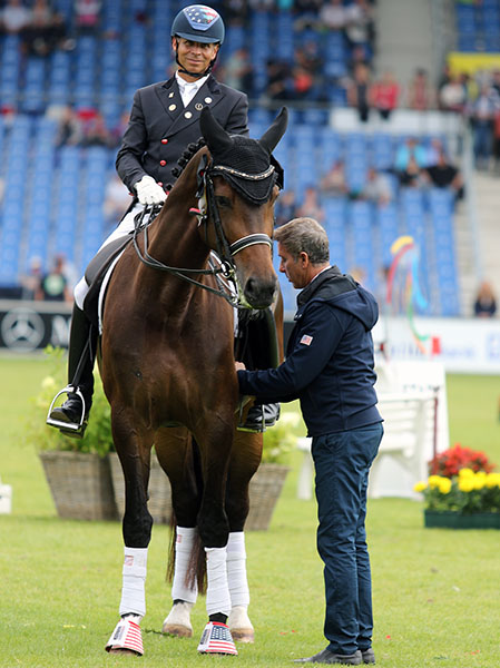 Robert Dover fixing the girth on Legolas with Steffen Peters in the saddle in the awards ceremony at the World Equestrian Festival CHIO in Aachen, Germany. © 2016 Ken Braddick/dressage-news.com